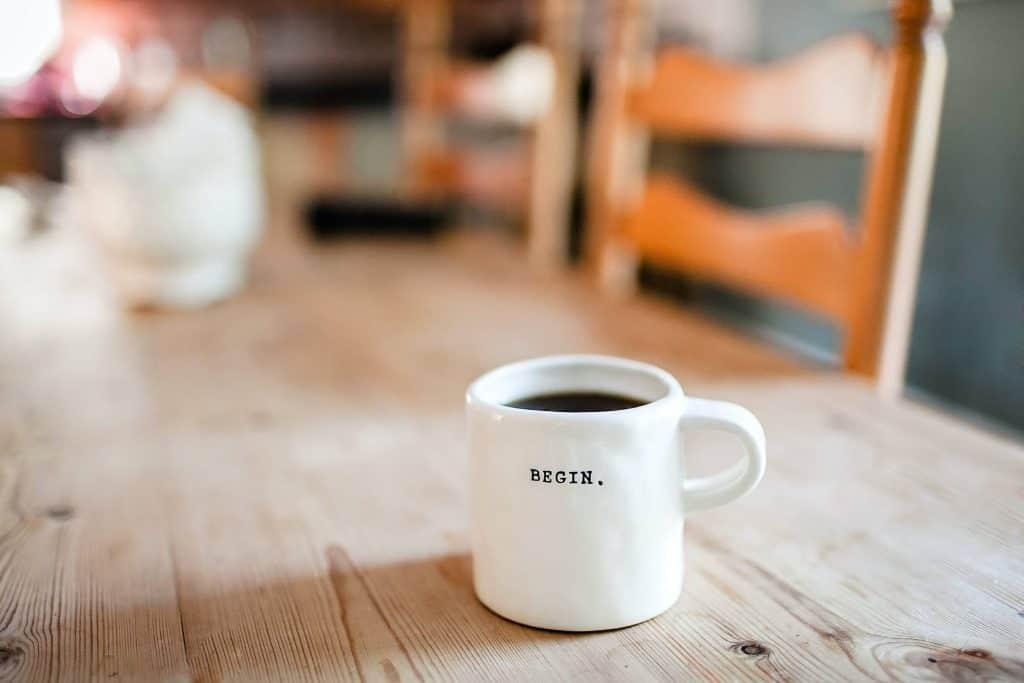 "Kubek kawy z napisem ""begin"""