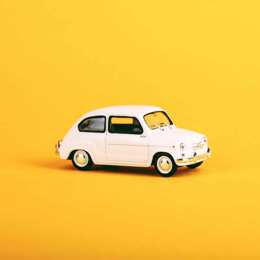 Małe białe autko na żółtym tle