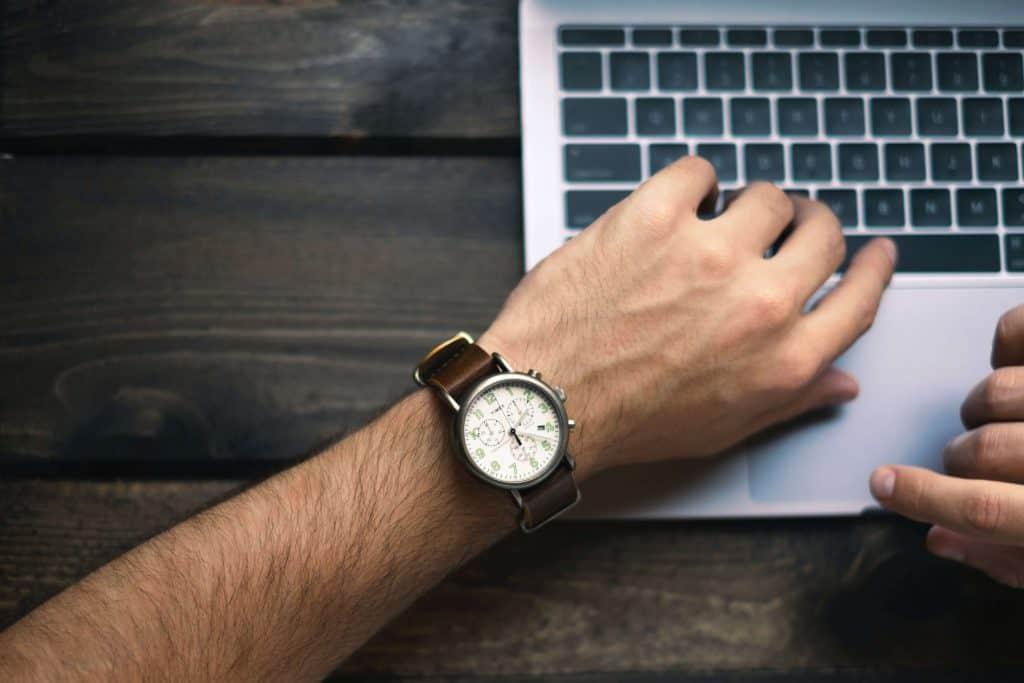 Dłoń z zegarkiem na laptopie