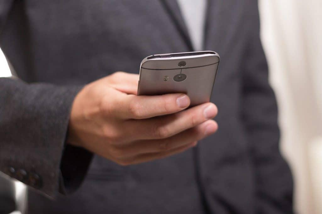Mężczyzna w garniturze trzymający telefon